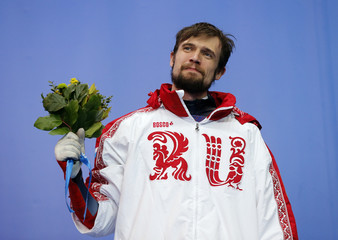 Russia's Alexander Tretiakov poses with his bouquet on the podium at the flower ceremony after winning the men's skeleton event at the 2014 Sochi Winter Olympics
