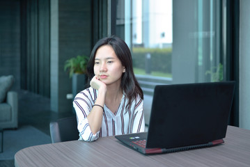 Stressed Casual Business Asian Woman thinking in front of  laptop in hotel
