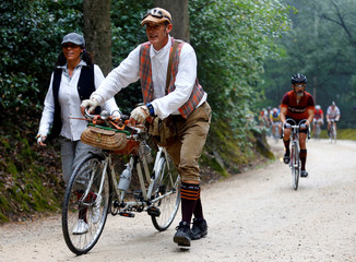 """Cyclists push their vintage tandem bicycle on gravel roads during the Strade Bianche section of the """"Eroica"""" cycling race for old bikes in Gaiole in Chianti"""