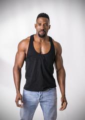Male black bodybuilder wearing dark tanktop on ripped muscular torso in studio shot on black background