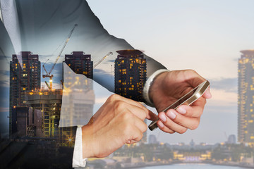 Double exposure of businessman use smartphone, construction crane and building in the evening, twilight as business, industrial, technology, telecommunication and Communication concept.