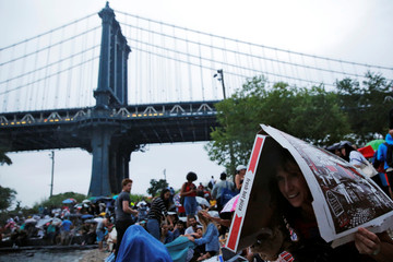 A woman uses a pizza box to shield herself from rain ahead of the Macy's 4th of July Fireworks on the East River in New York