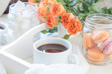 Orange mango macaroons, cup of coffee, marshmallow and fresh little roses on light wooden background. Sunlight. Coloring and processing photo with light vintage style. Shallow depth of field.