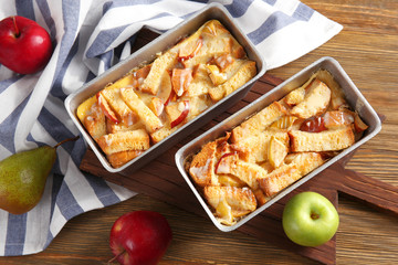 Freshly baked bread pudding in casserole dishes on wooden table