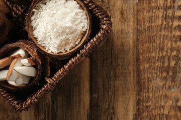 Wicker basket with coconut products on wooden background