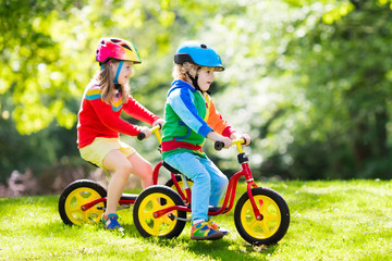 Kids ride balance bike in park