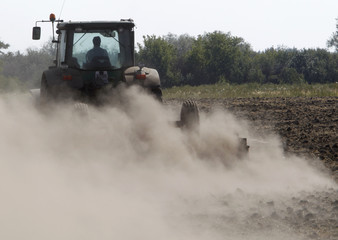 """An employee operates a tractor as he ploughs ground at the """"Vorobyevskoye Agro"""" collective farm some 250 km (155 miles) south-east of the city of Voronezh"""