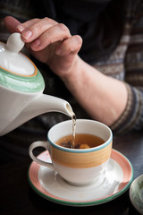 Woman pours tea from a kettle into a Cup