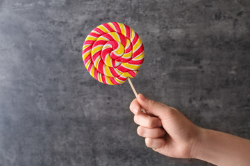 Female hand with tasty lollipop on dark background