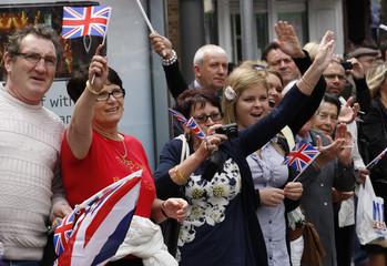 """Spectators cheer as British Army soldiers of the 1st Battalion """"Vikings"""", Royal Anglian Regiment, who recently returned from a combat tour in Afghanistan, march with bayonets fixed through the London suburb of Barking"""