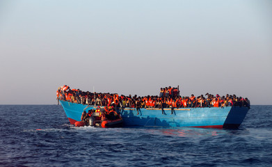 A rescue boat of the Spanish NGO Proactiva approaches an overcrowded wooden vessel with migrants from Eritrea, off the Libyan coast in Mediterranean Sea