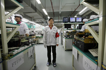 Huang Lixia from Shandong province poses as she works inside a Foxconn factory in the township of Longhua in the southern Guangdong province