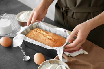 Woman holding baked pie in baking dish