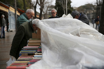 Men browse through books at a stall selling new and used books after light rain along Cuesta de Moyano pedestrian street in central Madrid