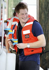 Britain's Prince Harry smiles as he leaves after a tour of Harbour Island in Nassau