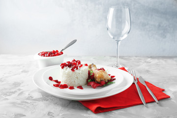 Portion of rice and chicken with cranberry sauce on plate