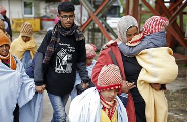 Migrants walk to board a train at the railway station in Tovarnik