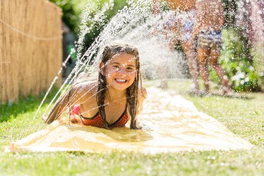 Water fun in garden - girl cooling down with water sprinkler