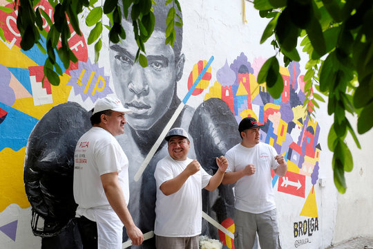 Employees of Joe's Pizza pose for a photograph after making a memorial to the late Muhammad Ali near a mural in New York