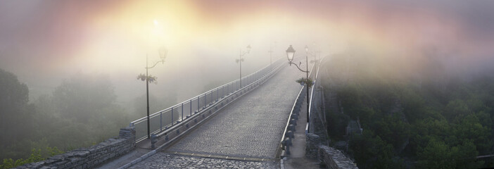 Papiers peints Pont Misty morning bridge over the river below the castle in Kamyanets-Podilsky on the background of the dawn mist gentle waves give the romantic charm of the legends of Ukrainian History..