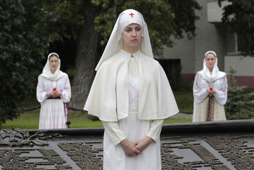 A woman dressed in a period nurse uniform attends the reburial of Russian soldiers fallen in World War One at a ceremony in Minsk