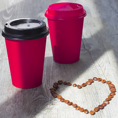 Bright red paper cups with coffee and beans of coffee   on a gray wooden background. The concept of street food.