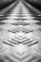 Background of metal with a repeating pattern, Вlack and white photography. Close-up, selective focus.