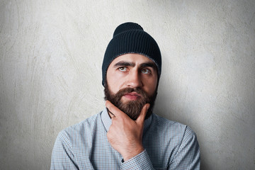 A studio portrait of stylish man with thick black beard wearing black cap and casual checked shirt having thoughtful look touching his beard thinking about someyhing while looking up.
