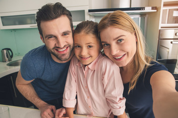 Young family smiling taking pictures together in kitchen