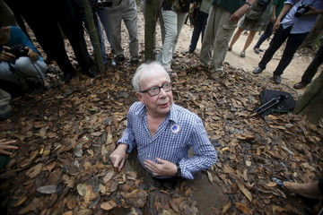 Scottish journalist James Pringle tries to enter the Cu Chi tunnel network through a hole camouflaged on the jungle floor during a guided tour near Ho Chi Minh City