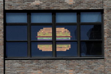 An image of a hamburger created with Post-it notes is seen in windows at 75 Varick street in lower Manhattan, New York