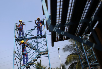 Students climb a scaffolding at an outdoor classroom at the Larsen & Toubro construction skills training institute in Panvel