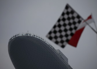 Chequered flags are decorate lamp posts as people look out from the Marina Bay Sands' sky park observatory deck ahead of the Singapore F1 night race in Singapore