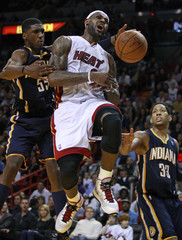 The Miami Heat's James is fouled by Indiana Pacers Hibbert as the Pacers Granger looks on during fourth quarter NBA basketball action in Miami