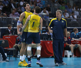 Brazil's Bruno and Junior celebrate a point against Italy next to their coach Rezende during their men's semi-final volleyball match at Earls Court during the London 2012 Olympic Games