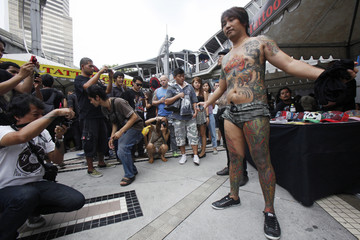 Rachata Pongphan shows off his tattoos as he joins the MBK Tattoo Contest 2012 at a shopping mall in Bangkok