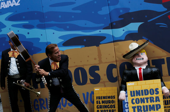 A member of the mariachi band jokes with his guitar next to a pinata depicting U.S. Republican presidential nominee Trump during a campaign encouraging U.S. citizens in Mexico to register to vote against Trump, in Mexico City