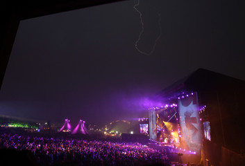 Canadian musician Neil Young and his band Crazy Horse perform during a thunder storm at the Paleo Festival in Nyon