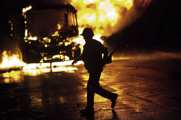 A man runs next to a bus on fire on a street in front of Pinheirinho slum where residents try to fight eviction attempts by police whom they expect to arrive with a court order, in Sao Jose dos Campos