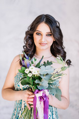 Beautiful girl bride brunette tresses make-up in a green lime dress with glitter sparkles with a delicate bouquet in hand looking at the camera with smile on white background close-up Studio portrait
