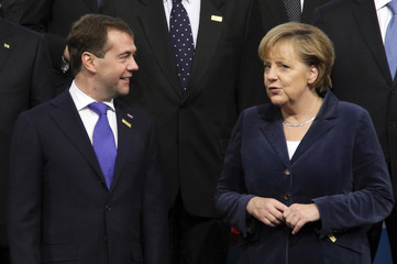 Russia's President Medvedev talks to Germany's Chancellor Merkel as they pose for a family photo during the OSCE Summit in Astana