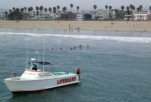 Lifeguard jumps into the water from a rescue boat to search for victims of a lightning strike that injured people in Venice, California