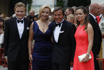 Trigema owner Grupp is flanked by family members as they arrive on the red carpet for the opening of the Bayreuth Wagner opera festival in Bayreuth
