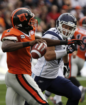 Toronto Argonauts Jason Pottinger chases BC Lions Casey Printers from the pocket during their CFL match in Vancouver