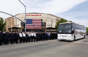 People salute as a bus leaves memorial for the Prescott Fire Department's Granite Mountain Hotshots team in Prescott Valley, Arizona