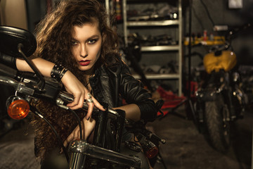 Beautiful young biker woman on her motorcycle at the workshop
