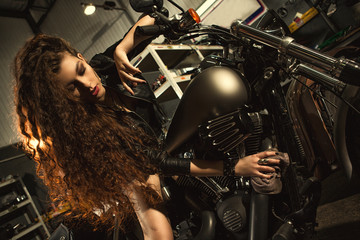 Gorgeous young woman polishing her motorbike at the workshop