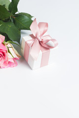 Gift box with pink ribbon with rose flowers on white table with copy space