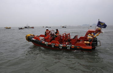"""Rescue workers operate near floats where the capsized passenger ship """"Sewol"""" sank, during the rescue operation in the sea off Jindo"""