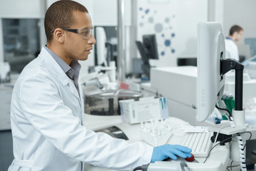 Professional scientist using computerized laboratory machine during the research